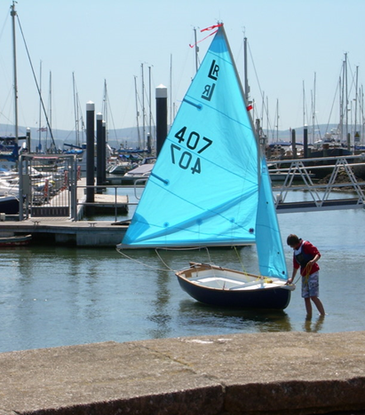 Small sailing boat with blue sails