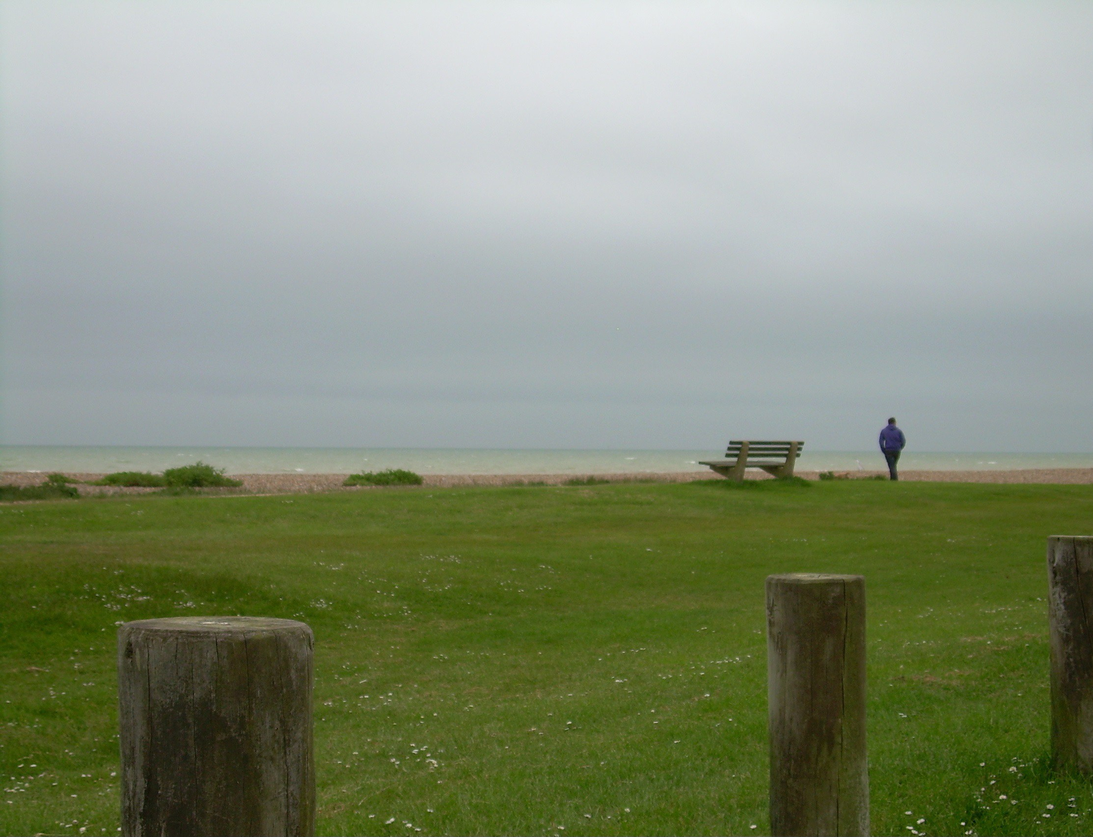 Man standing looking out to sea on a wet autumn day